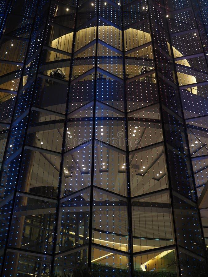 在玻璃镜子大厦角落的蓝色LED移动的轻的装饰,在晚上 免版税库存照片