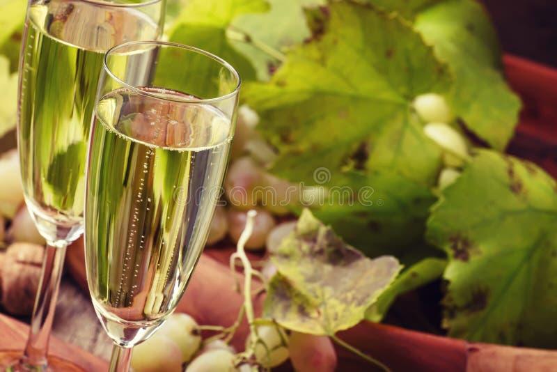 在玻璃,与藤,葡萄酒木背景的葡萄的香宾, 免版税库存照片