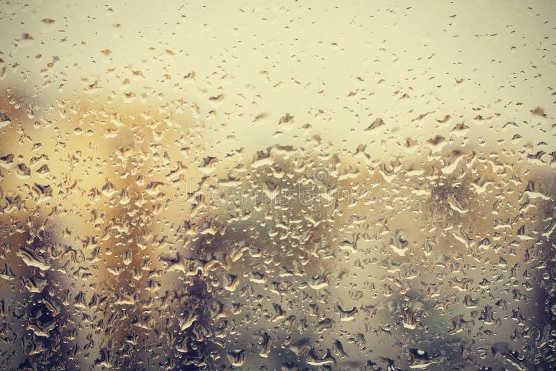 在玻璃,窗口大厦背景视图的雨珠在焦点外面的 免版税库存照片