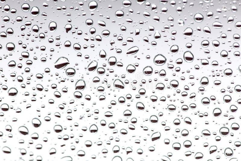 在玻璃,背景的雨下落 水下落背景textu 库存照片