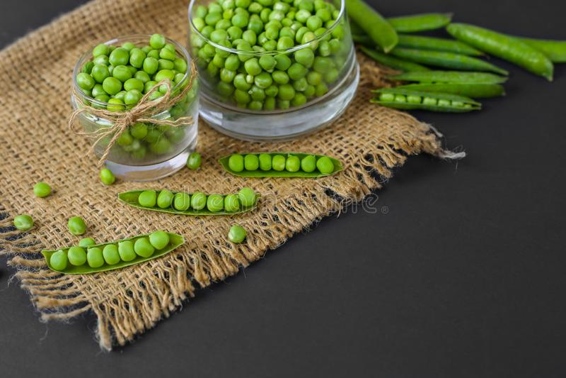 在玻璃,豌豆荚,疏散豌豆的绿豆,在黑背景 免版税库存图片