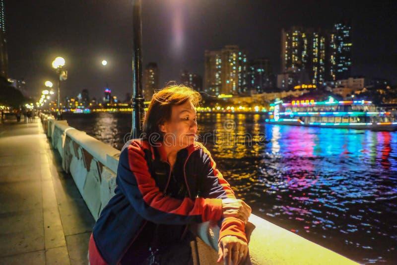 在珠江旁边的资深妇女旅客立场在广州市中国 库存照片