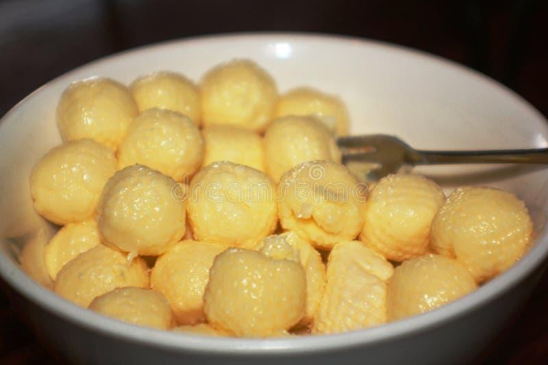 在球和叉子涂黄油在一个白色碗 库存照片