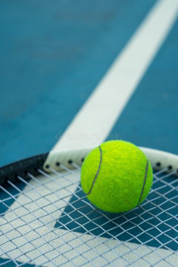 在球拍的网球有蓝色网球场的 库存图片
