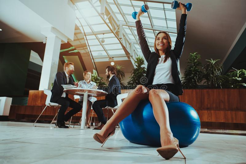 在球的妇女平衡与哑铃在办公室 免版税库存图片