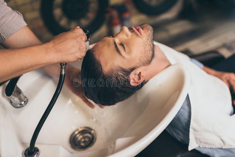 在理发师的播种的看法发式专家洗涤的客户头发 免版税库存照片