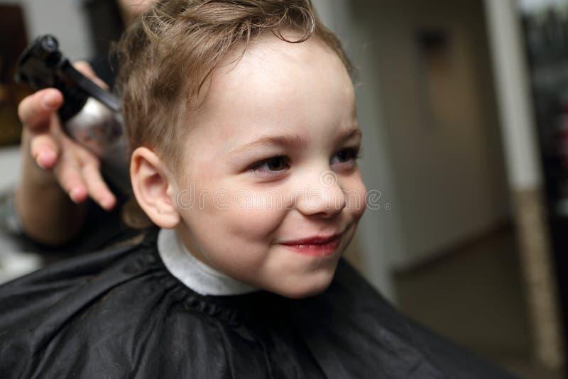 在理发店的微笑的孩子 库存照片