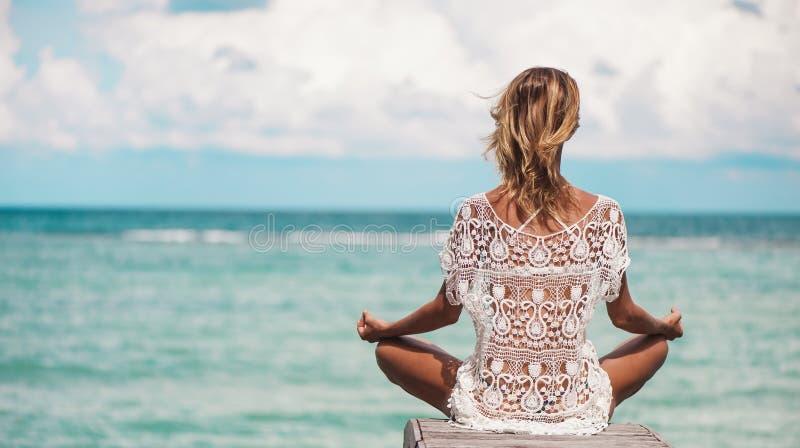 在瑜伽姿势的妇女凝思在海滩 免版税库存图片