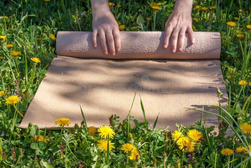 在瑜伽类以后供以人员滚动她的席子在一个绿色草甸在一个夏天晴天 免版税库存照片