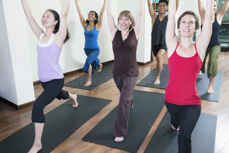 在瑜伽类期间,人用手提高了做瑜伽 库存照片