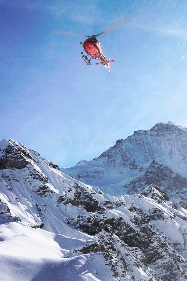 在瑞士高山山Mannlichen上的红色直升机飞行 库存照片