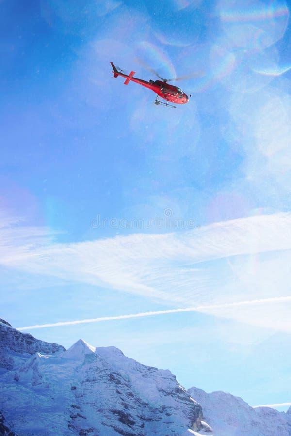 在瑞士高山山Mannlichen的红色直升机飞行在w 库存照片