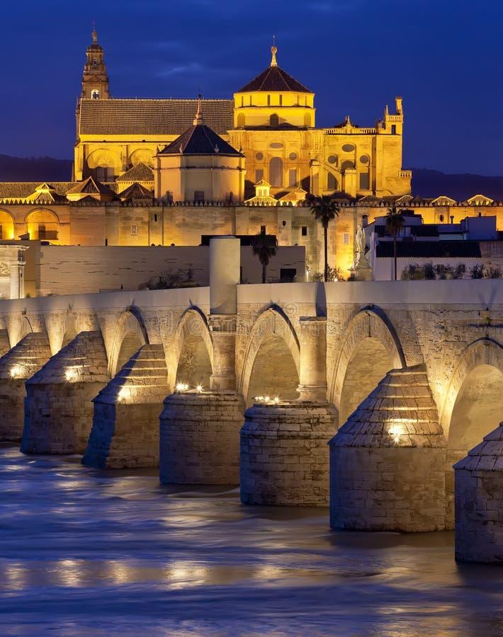 在瓜达尔基维尔河河和清真大寺(梅斯基塔大教堂)的罗马桥梁微明的在市科多巴,安大路西亚 免版税库存照片