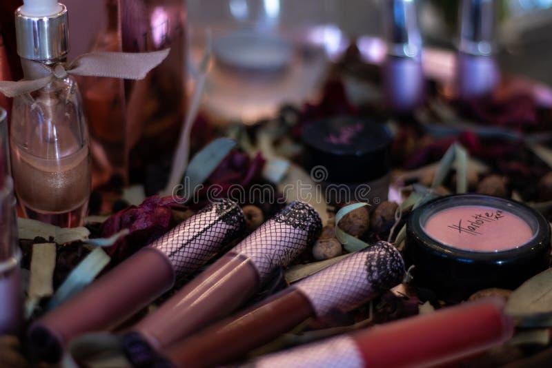 在瓣床上的被分类的美容品唇膏香水  免版税库存照片