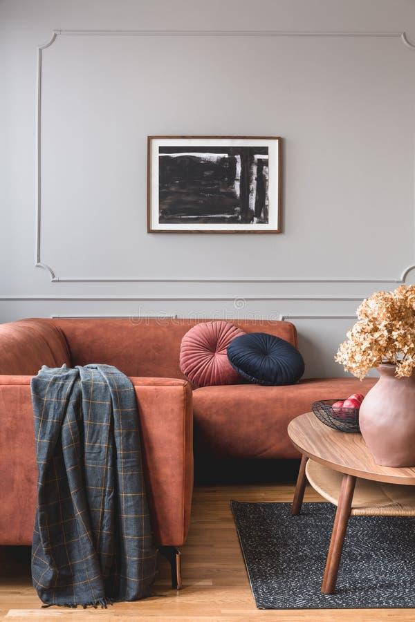 在瓦器花瓶的布朗花在时髦的咖啡桌上在别致的客厅内部与在灰色墙壁上的黑白海报 免版税库存图片