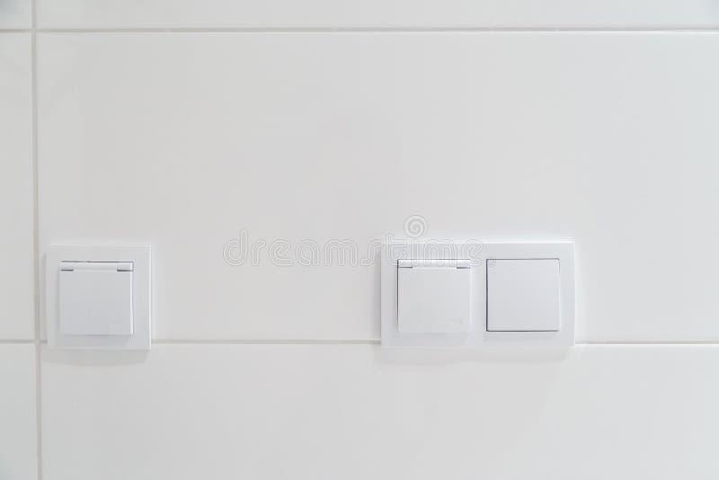 在瓦片白色墙壁上的现代电子开关  免版税库存照片