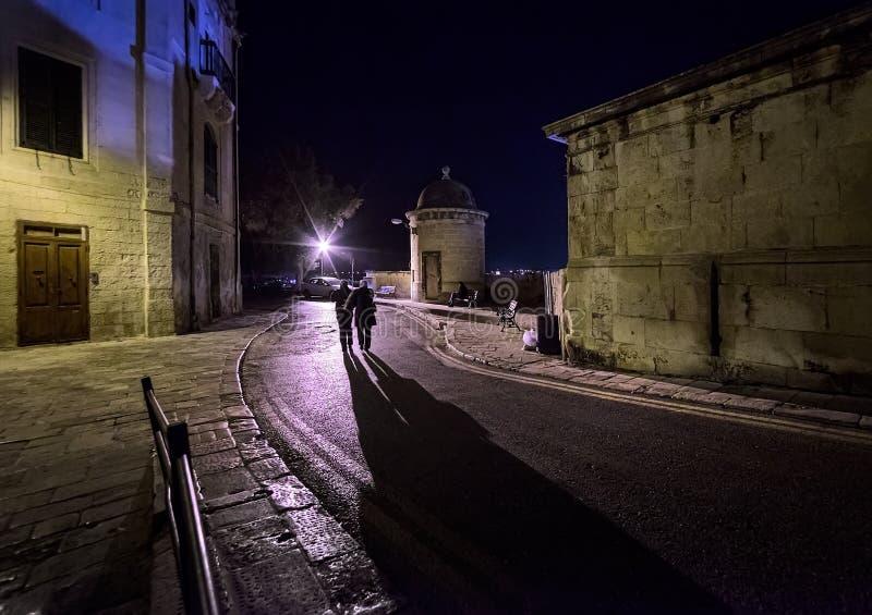 在瓦莱塔的黑暗的街道的步行 老城市的塔 马耳他 免版税库存图片