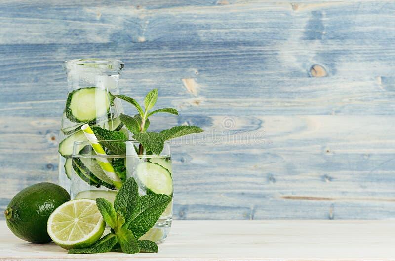 在瓶和玻璃的新鲜的凉快的柠檬水与泡影苏打水,石灰,黄瓜,薄菏,在浅兰的木板条的冰 图库摄影