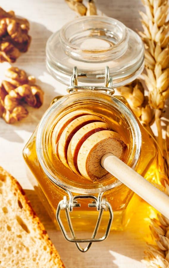 在瓶子、核桃、麦子和面包-农村早餐概念的蜂蜜浸染工 免版税库存图片