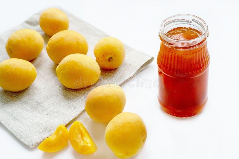 在瓶子和新鲜水果的杏子果酱在白色背景 免版税库存照片