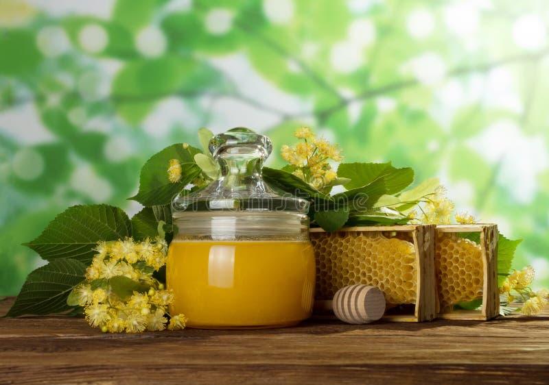 在瓶子用盒盖新鲜的蜂蜜,在蜂窝和花旁边在木桌上 免版税库存图片