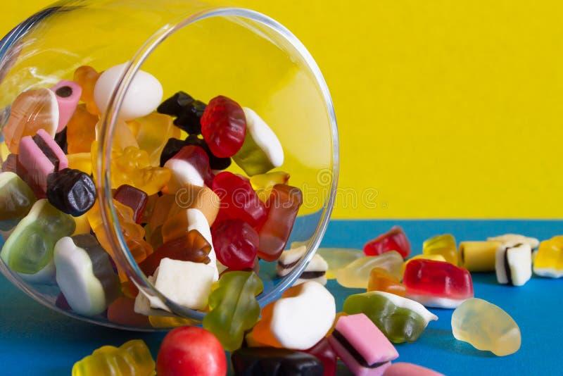 在瓶子的五颜六色的糖果在蓝色背景 库存图片