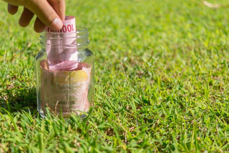 在瓶子的卢比纸币在绿色自然背景 免版税库存图片