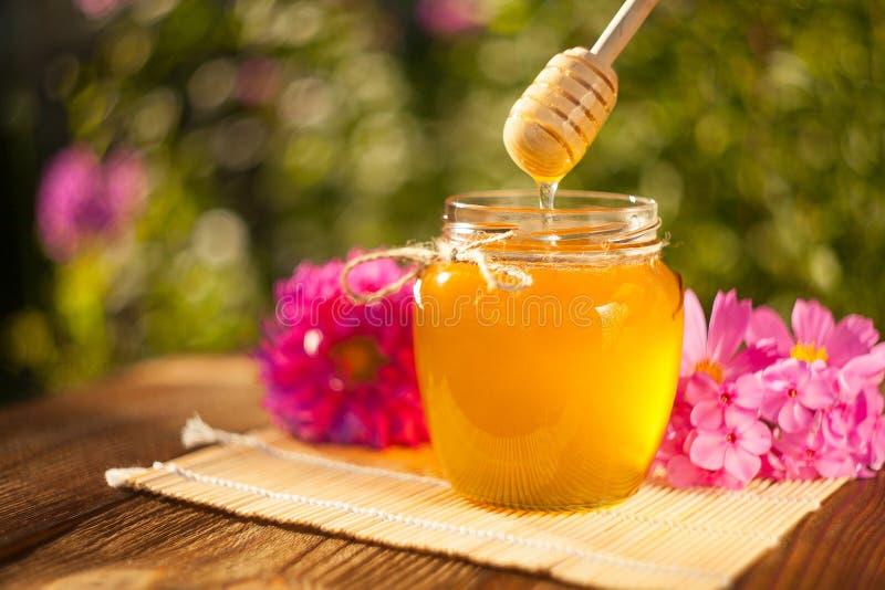 在瓶子的可口可口蜂蜜在桌上 免版税库存照片