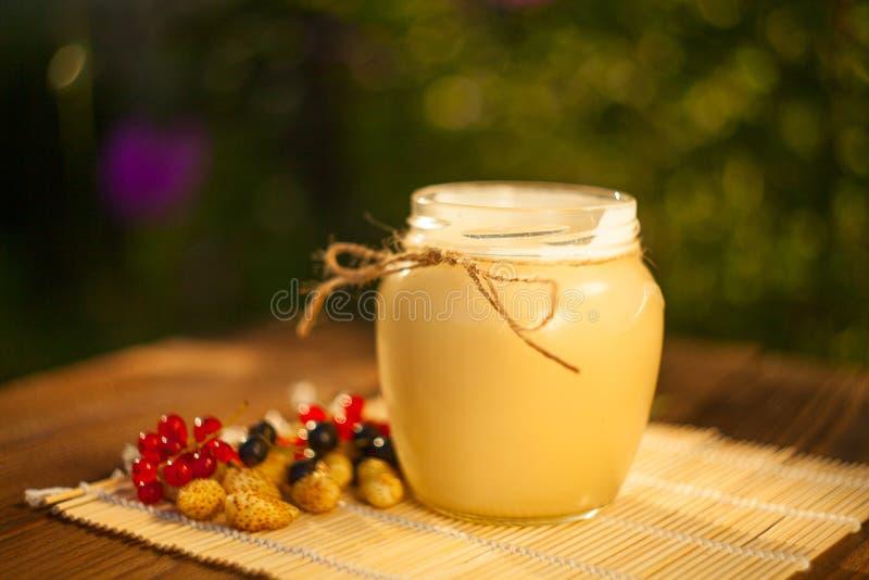 在瓶子的可口可口蜂蜜在桌上 免版税库存图片