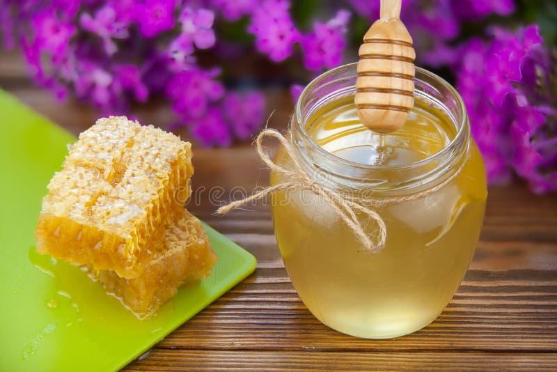 在瓶子的可口可口蜂蜜在桌上 免版税图库摄影
