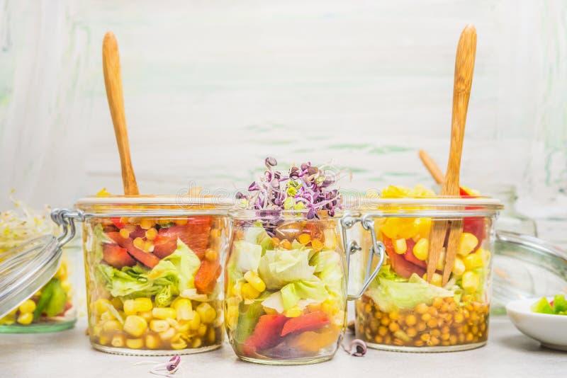 在瓶子的各种各样的沙拉干净的拿走吃光在轻的背景,关闭 免版税库存照片