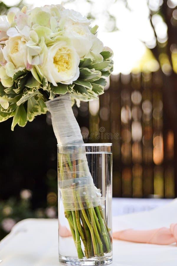 在瓶子的新娘花束在与白色,绿色和桃红色口音的表上 图库摄影
