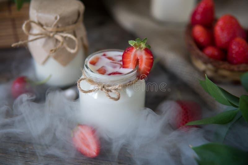 在瓶子的有机yougurt用草莓 与yo的新鲜的草莓 免版税库存照片