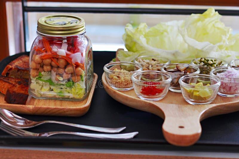 在瓶子的沙拉分层堆积与绿色,用切细的红萝卜、鸡豆、葱和蕃茄 库存照片