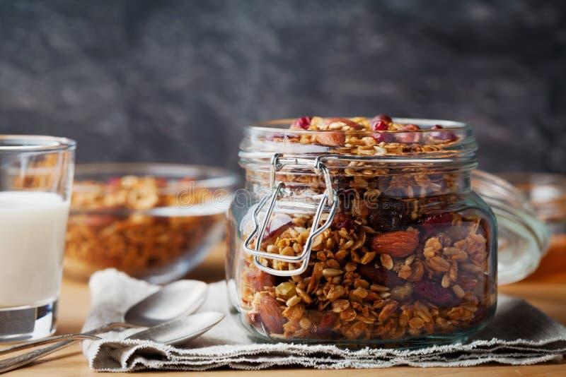 在瓶子的自创格兰诺拉麦片在土气桌、燕麦粥muesli健康早餐,坚果、种子和干果上 免版税库存图片