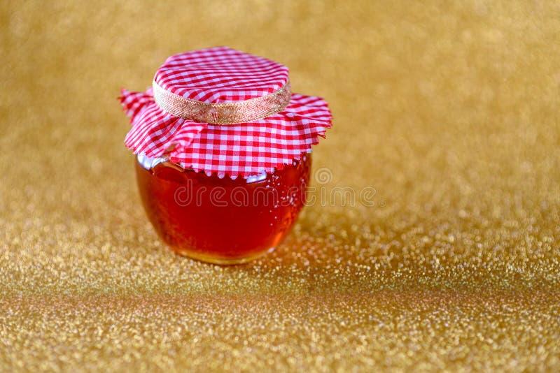 在瓶子的蜂蜜在金bokeh背景 库存图片