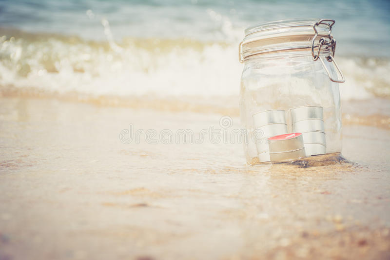 在瓶子的蜡烛有美丽的海滩的 库存照片