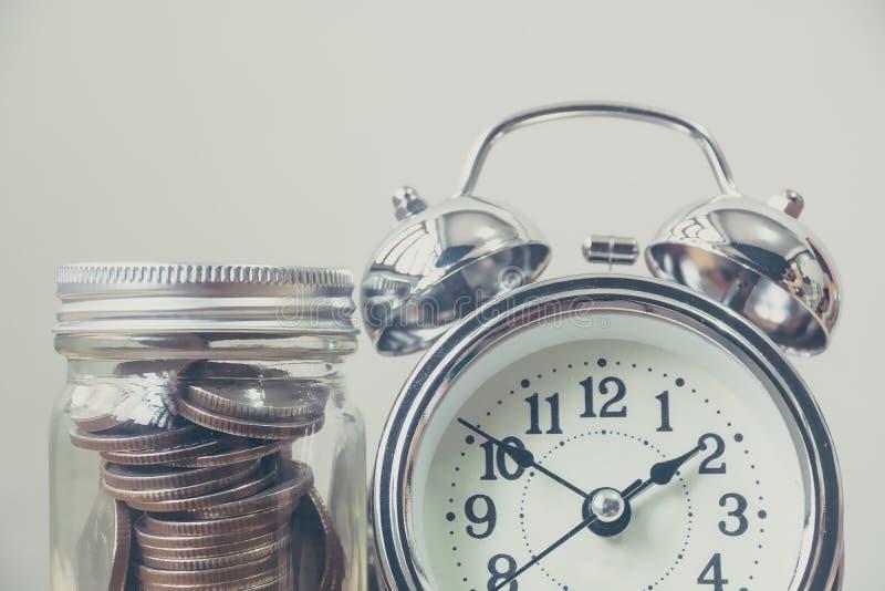 在瓶子的金钱硬币有时钟的,概念存金钱,并且时间处理 免版税库存图片