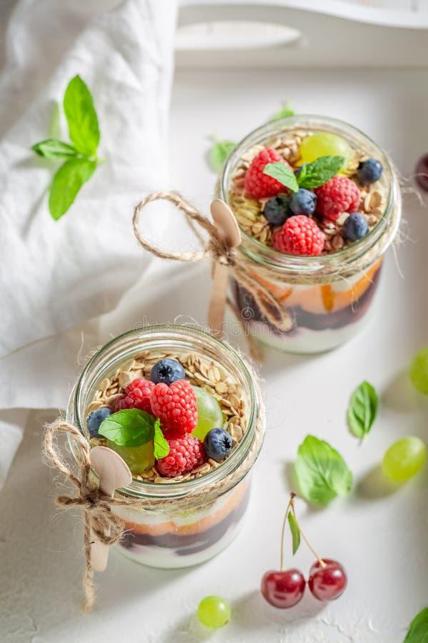 在瓶子的鲜美格兰诺拉麦片用酸奶和新鲜的莓果 免版税库存照片