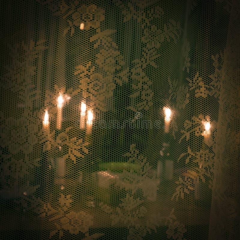 在瓶的一定数量的被点燃的蜡烛在透明花边窗帘后 免版税库存图片