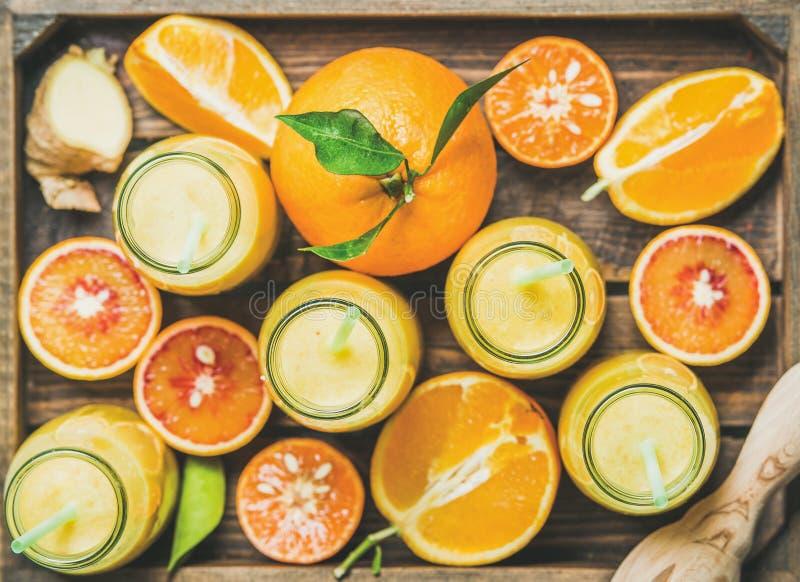 在瓶的健康黄色圆滑的人用在盘子的新鲜水果 免版税库存图片