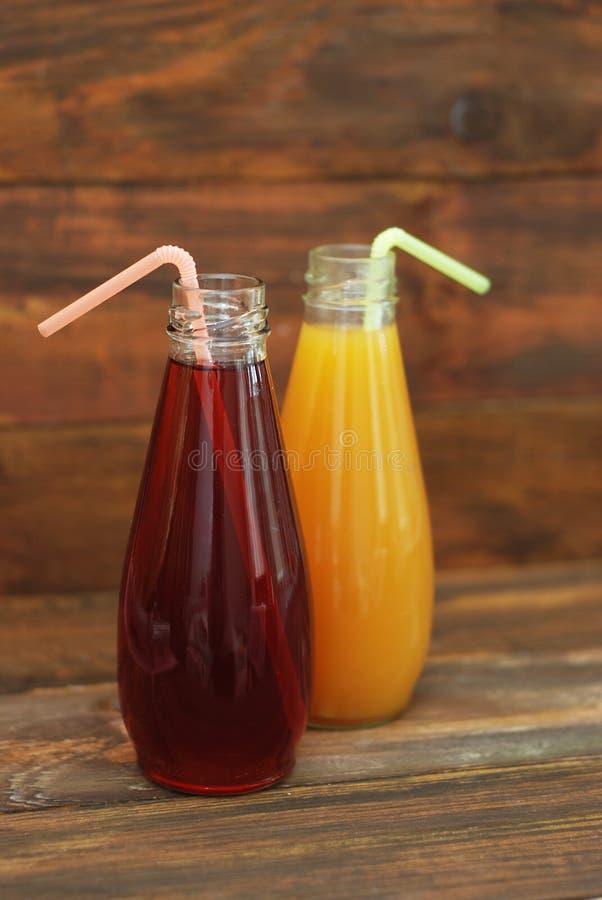 在瓶的可口橙色和红葡萄汁在土气木背景 垂直的图象 免版税库存照片