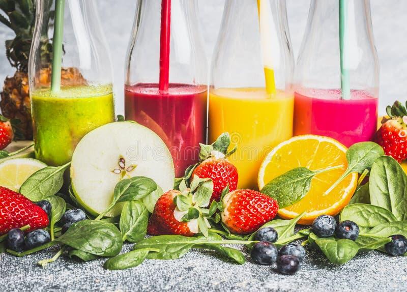 在瓶的各种各样的五颜六色的饮料有新鲜的有机成份的 健康圆滑的人或汁液用新鲜水果、莓果和veg 免版税库存照片