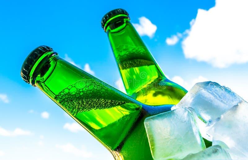 在瓶的啤酒有在冰块的泡影特写镜头的在蓝天背景 图库摄影