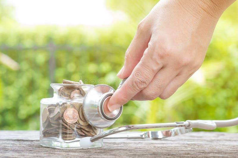 在瓶的在木背景的听诊器和硬币 概念为 库存图片