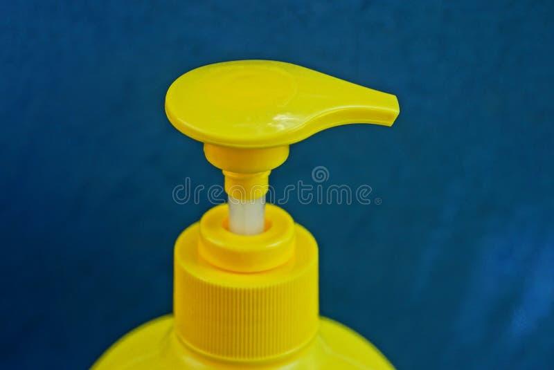 在瓶的塑料分配器在蓝色背景 库存照片