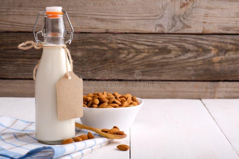 在瓶的杏仁牛奶有在土气木桌上的标签和杏仁坚果的 乳糖自由乳制品概念 图库摄影