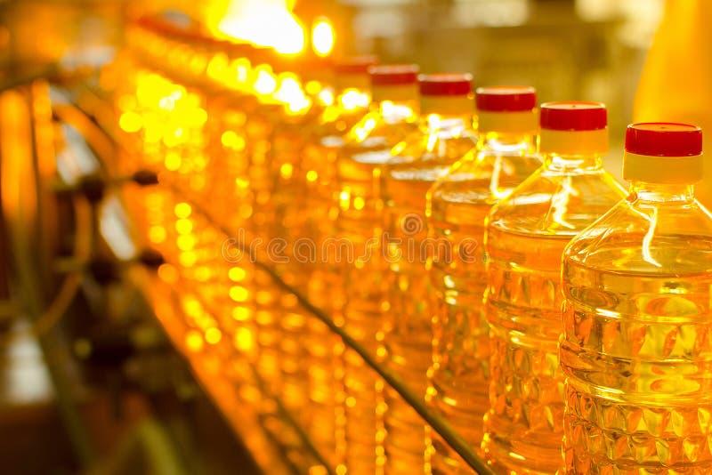 在瓶的油 向日葵油的工业生产 传动机 免版税图库摄影