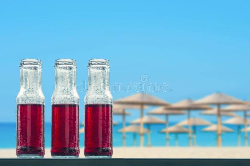 在瓶的石榴冷的汁在海滩和秸杆伞背景 免版税库存图片