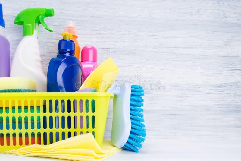 在瓶的篮子有清洁产品和一把刷子的,在右边有写的一个地方在轻的背景 免版税库存图片